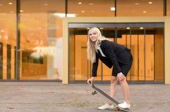 Sportliche junge blonde Frau mit einem Skateboard Lizenzfreies Stockbild