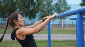 Sportliche junge Frau in der Sportkleidung zog auf die Stange draußen stock video