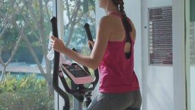 Sportliche junge Frau, die auf Schrittmaschine an der Eigentumswohnungsturnhalle trainiert stock video footage