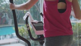 Sportliche junge Frau, die auf Schrittmaschine an der Eigentumswohnungsturnhalle trainiert stock video