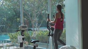 Sportliche junge Frau, die auf Schrittmaschine an der Turnhalle in der Zeitlupe trainiert stock footage