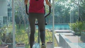 Sportliche junge Frau, die auf Schrittmaschine an der Turnhalle in der Zeitlupe trainiert stock video
