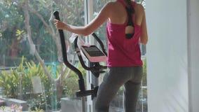 Sportliche junge Frau, die auf Schrittmaschine an der Turnhalle in der Zeitlupe trainiert stock video footage