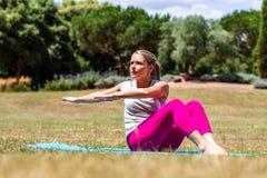Sportliche junge Frau, die herauf ihre Arme im Park tont Lizenzfreies Stockfoto