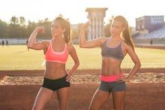 Sportliche junge Frauen mit den perfekten Körpern, die Bizepse zeigen stockbild