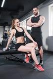 Sportliche kaukasische Paare von den Athleten, die an der Turnhalle aufwerfen lizenzfreie stockfotografie