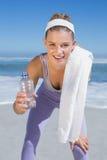 Sportliche lächelnde blonde Stellung auf dem Strand mit Tuch und Flasche Stockfoto