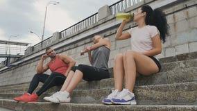 Sportliche Leute, die an der Treppe sich entspannen stock video