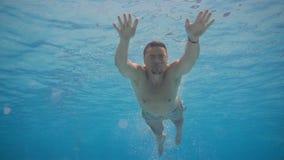 Sportliche Mannschwimmen unter dem Wasser Junger aktiver Schwimmer, der im Pool taucht