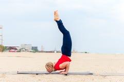 Sportliche schöne blonde Frau in der Sportkleidung zuhause ausarbeitend, Yogakinnbalance Ganda Bherundasana oder Skorpion tuend Lizenzfreie Stockfotografie
