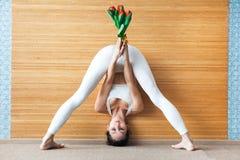 Sportliche schöne junge Frau in einem übenden Yoga der weißen Klage, Grifftulpen, stehende Straddle-Rumpfbeuge-Haltung tuend, Pra Stockbilder