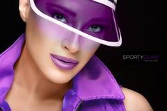 Sportliche Schönheit Moderne junge Frau in der purpurroten Sonnenblende Stockfoto