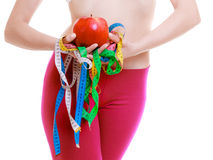 Sportliche Sitzfrau mit Maß nimmt Frucht auf. Zeit für das Diätabnehmen. Stockbilder