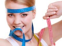 Sportliche Sitzfrau mit Maßbändern. Zeit für das Diätabnehmen. stockfotografie