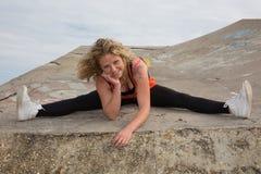 Sportliche starke nehmen ab und passen das Sitzen der jungen Frau und tun Spalte Stockfotografie