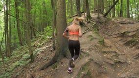 Sportliche und aktive hübsche Frau, die auf Forest Path Uphill, hintere Ansicht läuft stock footage