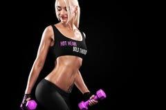 Sportliche und geeignete blonde Frau mit rosa Dummkopf trainierend am schwarzen Hintergrund, um geeignet zu bleiben Crossfit-Trai Stockbilder