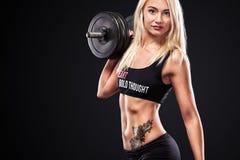 Sportliche und geeignete Schönheit mit Dummkopf trainierend am schwarzen Hintergrund, um geeignet zu bleiben Fitnwss-Trainingsmot lizenzfreies stockfoto