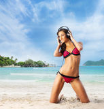Sportliche und sexy Frau, die auf dem Strand sich entspannt Lizenzfreie Stockbilder