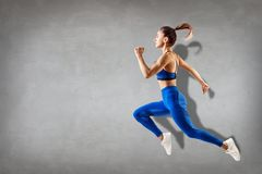 Sportlicher Betrieb und Springen der jungen Frau Stockbild