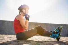 Sportlicher blonder Schlittschuhläufer, der auf dem Boden und befestigendem Sturzhelm sitzt Lizenzfreies Stockfoto
