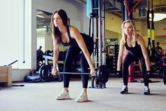 Sportlicher Brunette und blonde Frauen, die Übungen mit Barbell in einem Turnhallenclub tun Stockfotografie