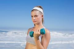 Sportlicher fokussierter blonder anhebender Dummkopf auf dem Strand Lizenzfreie Stockfotos
