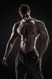 Sportlicher gesunder Mann, der sein perfektes boddy aufwirft und zeigt Stockfotografie