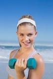 Sportlicher glücklicher blonder anhebender Dummkopf auf dem Strand Stockfotografie