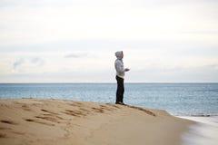 Sportlicher junger Mann, der auf dem Strand beim Machen der Pause während des Trainings steht Lizenzfreies Stockfoto