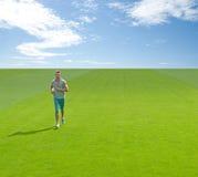 Sportlicher junger Mann, der auf grünes Feld läuft stockfoto