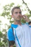 Sportlicher junger Mann, der seinen Kopfhörer während des Rüttelns justiert Stockbilder