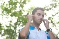 Sportlicher junger Mann, der seinen Kopfhörer während des Rüttelns justiert Lizenzfreies Stockfoto
