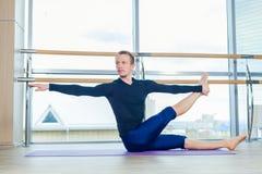 Sportlicher junger Mann, der, Yoga, pilates, Eignungstraining, stehend in asana eka pada adho mukha svanasana, eins ausarbeitet Stockfoto
