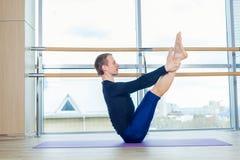 Sportlicher junger Mann, der, Yoga, pilates, Eignungstraining, stehend in asana eka pada adho mukha svanasana, eins ausarbeitet Stockbild