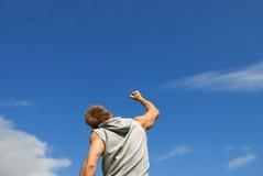 Sportlicher junger Mann mit seinem Arm hob in Freude an Stockfotografie