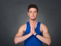 Sportlicher junger Mann in Namaste-Position mit muskulösem Körper Stockfotos