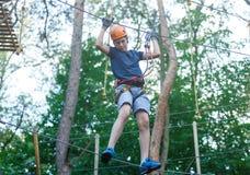 Sportlicher, junger, netter Junge im weißen T-Shirt verbringt seine Zeit im Abenteuerseilpark im Sturzhelm und in der sicheren Au stockfoto