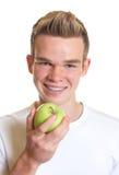 Sportlicher Kerl, der einen Apfel zeigt Lizenzfreies Stockfoto