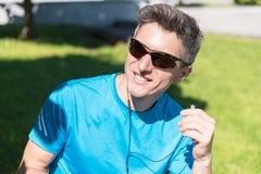 Sportlicher Kerl, der Musik bei der Ausbildung hört Stockfotos