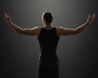 Sportlicher Kerl steht in der Dunkelheit und im Achselzucken Stockbild