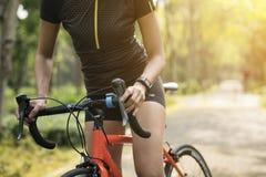 Sportlicher Mädchenradfahrer, der mit Fahrrad im Wald aufwirft stockfotos