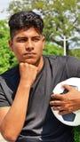 Sportlicher männlicher Fußball-Spieler, der eine Entscheidung trifft Stockfotografie