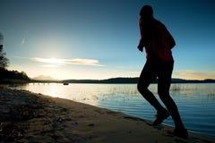 Sportlicher Mann, der den Morgen rüttelt auf Seestrand an den hellen Sonnenaufgang-Schattenbildern tut Stockfotografie
