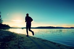 Sportlicher Mann, der den Morgen rüttelt auf Seestrand an den hellen Sonnenaufgang-Schattenbildern tut Lizenzfreies Stockfoto