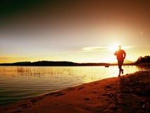 Sportlicher Mann, der den Morgen rüttelt auf Seestrand an den hellen Sonnenaufgang-Schattenbildern tut Lizenzfreies Stockbild