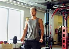 Sportlicher Mann in der Sportkleidung hält Barbell über TRX-Standhintergrund in einem Turnhallenclub Stockbilder