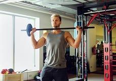 Sportlicher Mann in der Sportkleidung hält Barbell über TRX-Standhintergrund in einem Turnhallenclub Lizenzfreie Stockbilder
