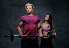 Sportlicher Mann hält Barbellgewicht und weibliches Modell O der dünnen Eignung Stockfotos