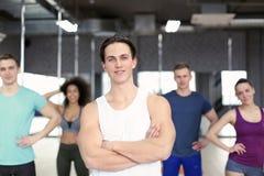 Sportlicher Mann mit Gruppe Athleten in der Turnhalle lizenzfreie stockbilder